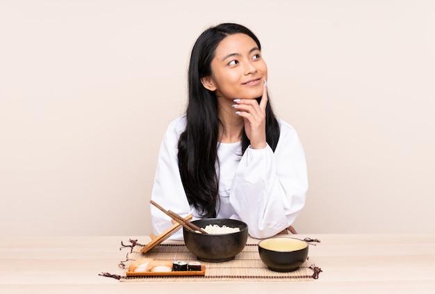 Ragazza asiatica dell'adolescente che mangia alimento asiatico isolato sulla parete beige che pensa un'idea mentre cercando