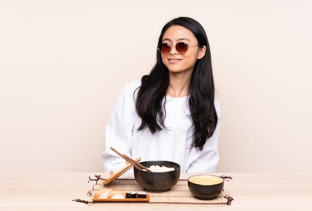 Ragazza asiatica dell'adolescente che mangia alimento asiatico isolato sulla parete beige con i vetri e felice