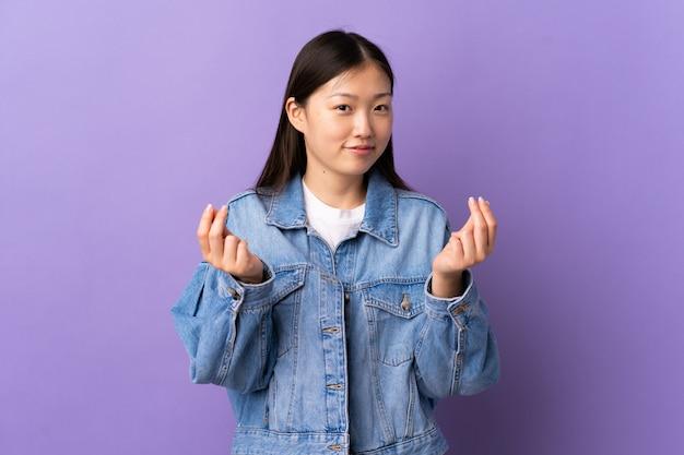 Ragazza asiatica dell'adolescente che mangia alimento asiatico isolato sulla parete beige con espressione facciale colpita