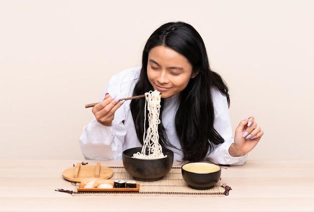 Ragazza asiatica dell'adolescente che mangia alimento asiatico isolato sul beige