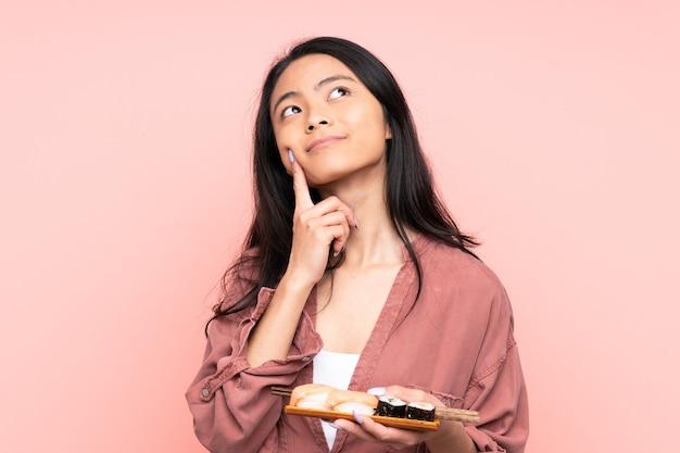 Ragazza asiatica dell'adolescente che mangia i sushi isolati sul colore rosa che pensa un'idea