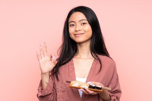Ragazza asiatica dell'adolescente che mangia i sushi isolati sulla parete rosa che mostra un segno giusto con le dita