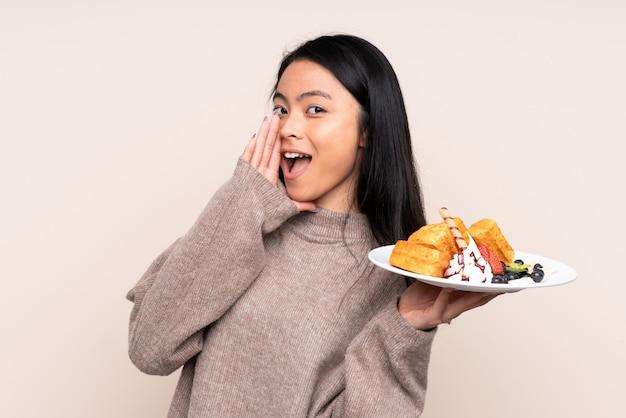Cialde asiatiche della tenuta della ragazza dell'adolescente sulla parete beige che gridano con la bocca spalancata