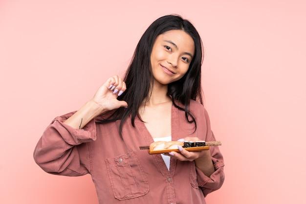 Donna asiatica dell'adolescente che mangia sushi isolato sul rosa orgoglioso