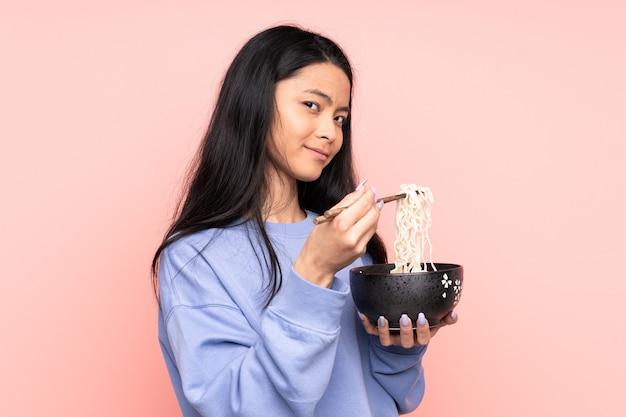 Donna asiatica dell'adolescente isolata sul beige che tiene una ciotola di tagliatelle con le bacchette
