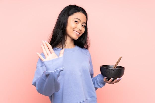 Donna asiatica dell'adolescente isolata sul beige che saluta con la mano con l'espressione felice mentre tiene una ciotola di tagliatelle con le bacchette