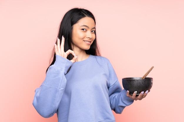 Donna asiatica dell'adolescente isolata sul beige che mostra segno giusto con le dita mentre tiene una ciotola di tagliatelle con le bacchette