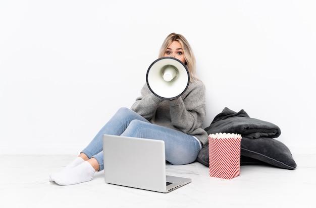 Ragazza bionda dell'adolescente che mangia popcorn mentre guardando un film sul computer portatile che grida tramite un megafono