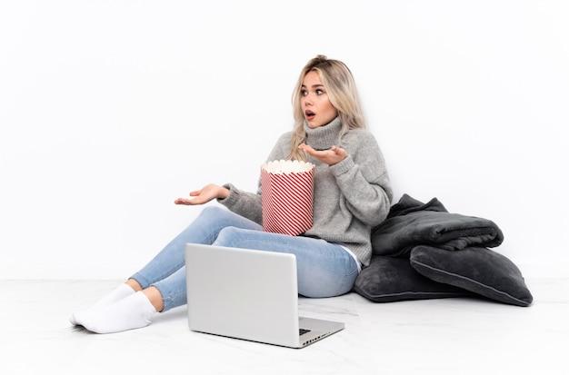 Ragazza bionda dell'adolescente che mangia popcorn mentre guarda un film sul computer portatile con l'espressione facciale di sorpresa