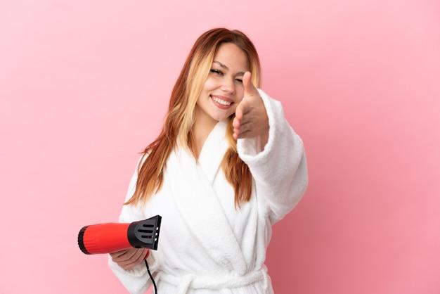 Ragazza bionda adolescente che tiene un asciugacapelli su sfondo rosa isolato che stringe la mano per aver chiuso un buon affare a