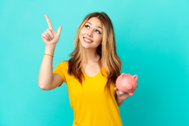 Ragazza bionda dell'adolescente che tiene un salvadanaio sopra fondo blu isolato che indica con il dito indice una grande idea
