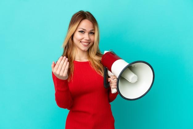 Ragazza bionda dell'adolescente sopra fondo blu isolato che tiene un megafono e che invita a venire con la mano