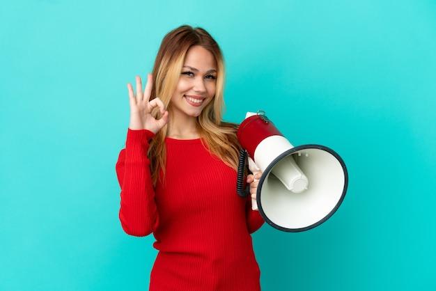 Ragazza bionda dell'adolescente sopra fondo blu isolato che tiene un megafono e che mostra il segno giusto con le dita
