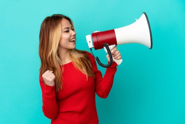 Ragazza bionda adolescente su sfondo blu isolato che grida attraverso un megafono per annunciare qualcosa in posizione laterale in