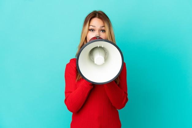 Ragazza bionda dell'adolescente sopra fondo blu isolato che grida tramite un megafono per annunciare qualcosa