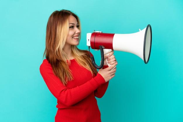Ragazza bionda dell'adolescente sopra la parete blu isolata che grida tramite un megafono per annunciare qualcosa