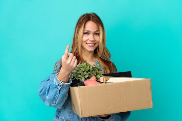 Adolescente ragazza bionda che fa una mossa mentre prende una scatola piena di cose che fanno un gesto imminente