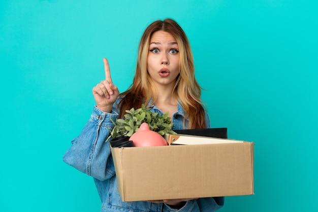Adolescente ragazza bionda che fa una mossa mentre prende una scatola piena di cose con l'intenzione di realizzare la soluzione mentre alza un dito