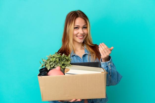 Ragazza bionda adolescente che fa una mossa mentre prende una scatola piena di cose che invitano a venire con la mano. felice che tu sia venuto