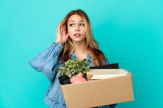 Adolescente ragazza bionda che fa una mossa mentre prende una scatola piena di cose ascoltando qualcosa mettendo la mano sull'orecchio