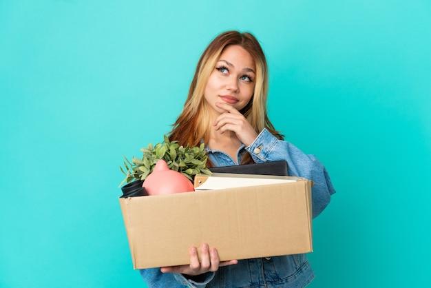 Ragazza bionda adolescente che fa una mossa mentre prende una scatola piena di cose e guarda in alto