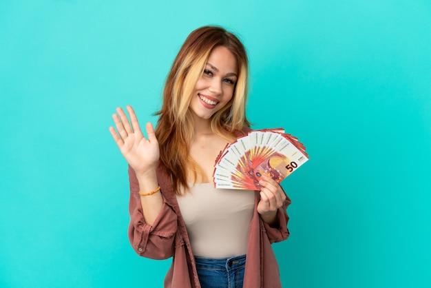 Ragazza bionda dell'adolescente che prende molti euro sopra fondo blu isolato che saluta con la mano con l'espressione felice