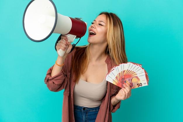 Ragazza bionda dell'adolescente che prende molti euro sopra fondo blu isolato che grida tramite un megafono