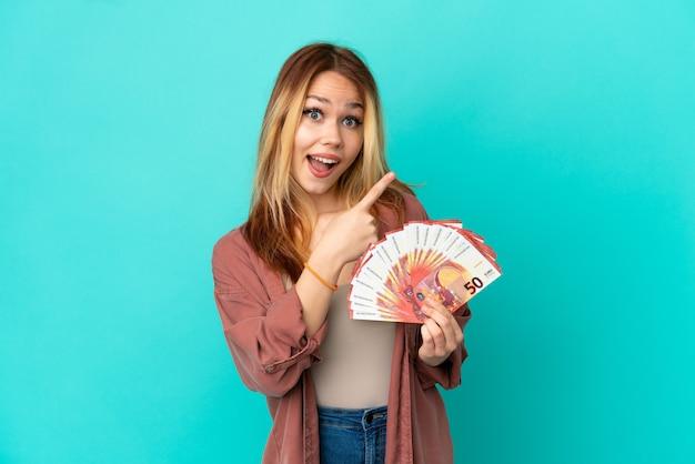 Ragazza bionda dell'adolescente che prende molti euro sopra fondo blu isolato sorpreso e che indica side