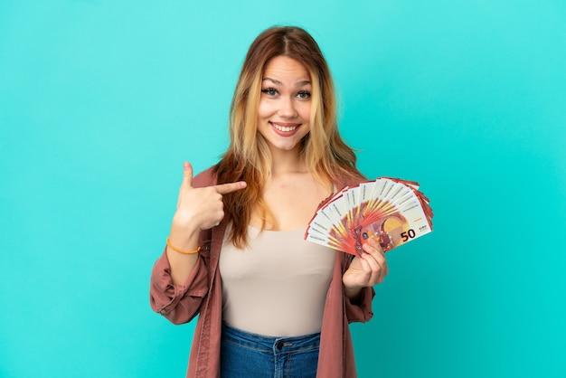 Ragazza bionda dell'adolescente che prende molti euro sopra fondo blu isolato con l'espressione facciale di sorpresa