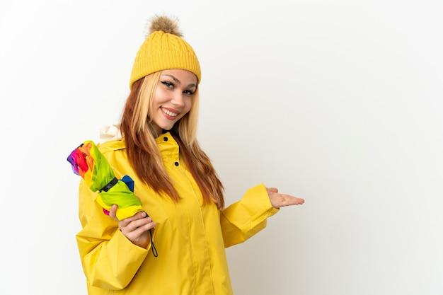 Adolescente ragazza bionda che indossa un cappotto antipioggia su sfondo bianco isolato estendendo le mani di lato per invitare a venire