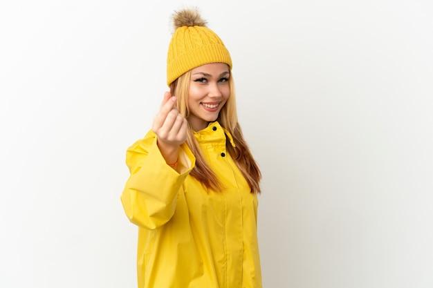 Ragazza bionda dell'adolescente che indossa un cappotto antipioggia sopra fondo bianco isolato che fa il gesto dei soldi