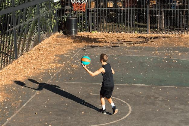 Giocatore di pallacanestro del ragazzo dell'adolescente che dribbla sul campo sportivo