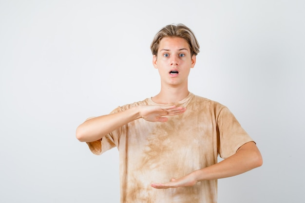 Ragazzo adolescente che mostra il segno di taglia in maglietta e sembra perplesso, vista frontale.