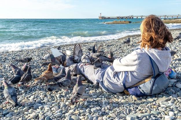Ragazzo dell'adolescente che si siede alla costa della spiaggia dal mare e che dà da mangiare ai piccioni - concetto di felicità