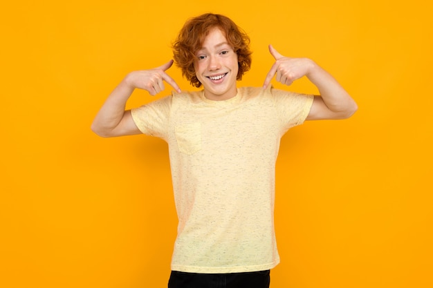 Il ragazzo dell'adolescente in una maglietta con una disposizione mostra un'iscrizione di pubblicità su esso su giallo con lo spazio della copia