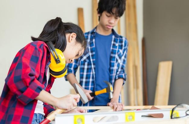 Ragazzo dell'adolescente con la sua sorellina che costruisce insieme un'officina in un'officina di falegnameria. squadra di bambini nel laboratorio artigianale