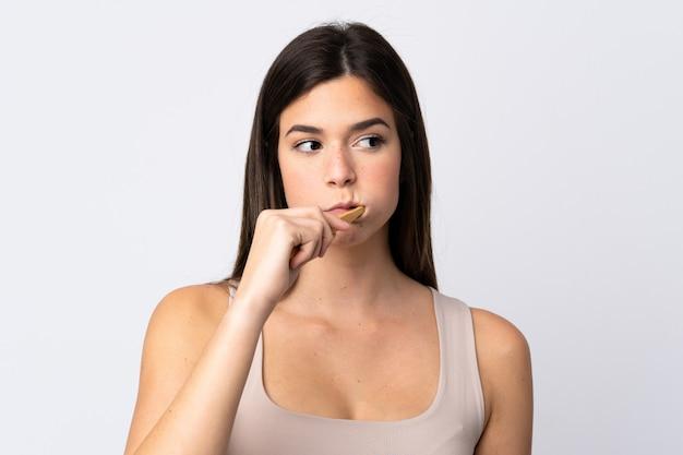 Ragazza brasiliana dell'adolescente che pulisce i suoi denti sopra fondo bianco isolato