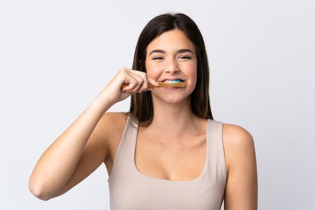 Ragazza brasiliana dell'adolescente che pulisce i suoi denti sopra la parete bianca isolata