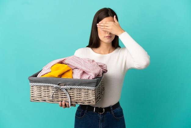 Adolescente ragazza brasiliana che tiene un cesto di vestiti isolato su sfondo blu che copre gli occhi con le mani. non voglio vedere qualcosa