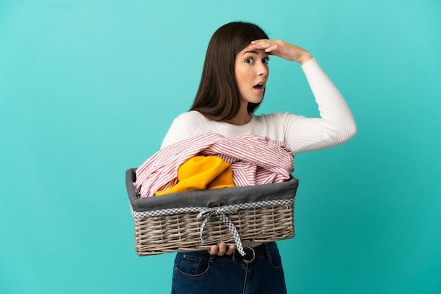 Adolescente ragazza brasiliana che tiene un cesto di vestiti isolato su sfondo blu facendo un gesto a sorpresa mentre guarda di lato