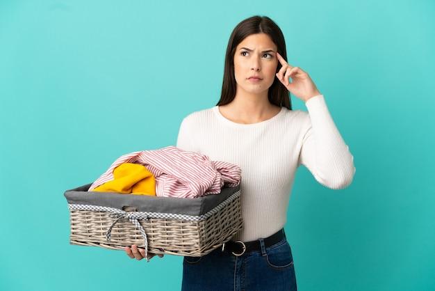Ragazza brasiliana dell'adolescente che tiene un cestino dei vestiti isolato su priorità bassa blu che ha dubbi e pensiero