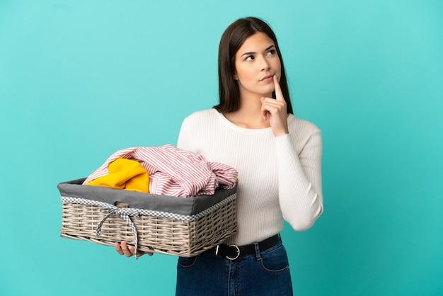 Ragazza brasiliana dell'adolescente che tiene un cestino dei vestiti isolato su priorità bassa blu che ha dubbi mentre osserva in su
