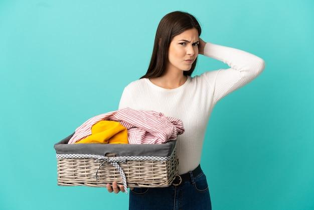 Ragazza brasiliana dell'adolescente che tiene un cestino dei vestiti isolato su priorità bassa blu che ha dubbi