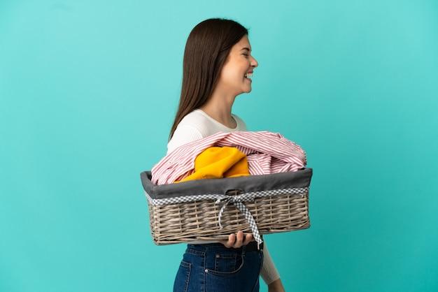 Ragazza brasiliana dell'adolescente che tiene un cestino dei vestiti isolato su priorità bassa blu che ride in posizione laterale