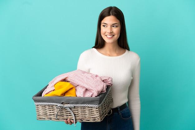 Ragazza brasiliana dell'adolescente che tiene un cestino dei vestiti isolato su priorità bassa blu che osserva al lato e che sorride