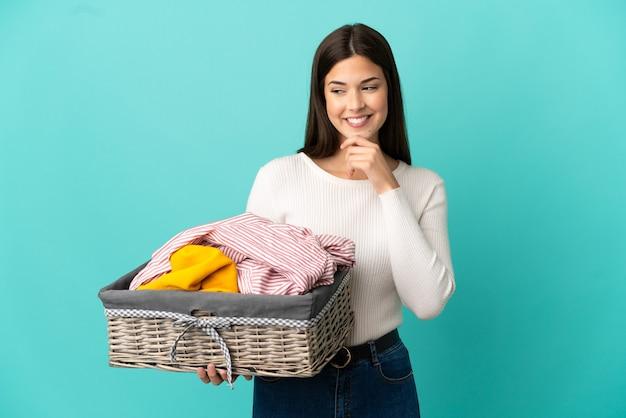 Adolescente ragazza brasiliana che tiene un cesto di vestiti isolato su sfondo blu guardando di lato e sorridente