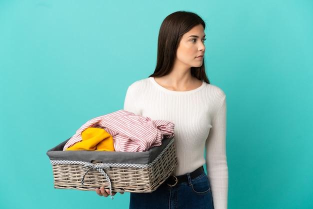 Ragazza brasiliana dell'adolescente che tiene un cestino dei vestiti isolato su priorità bassa blu che osserva al lato