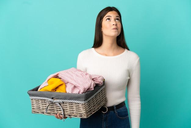 Ragazza brasiliana dell'adolescente che tiene un cestino dei vestiti isolato su priorità bassa blu e che osserva in su