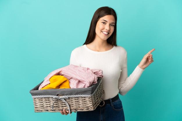 Ragazza brasiliana dell'adolescente che tiene un cestino dei vestiti isolato su priorità bassa blu che indica il dito a lato