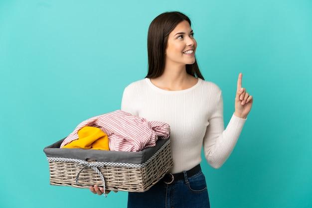 Adolescente ragazza brasiliana che tiene un cesto di vestiti isolato su sfondo blu che indica una grande idea